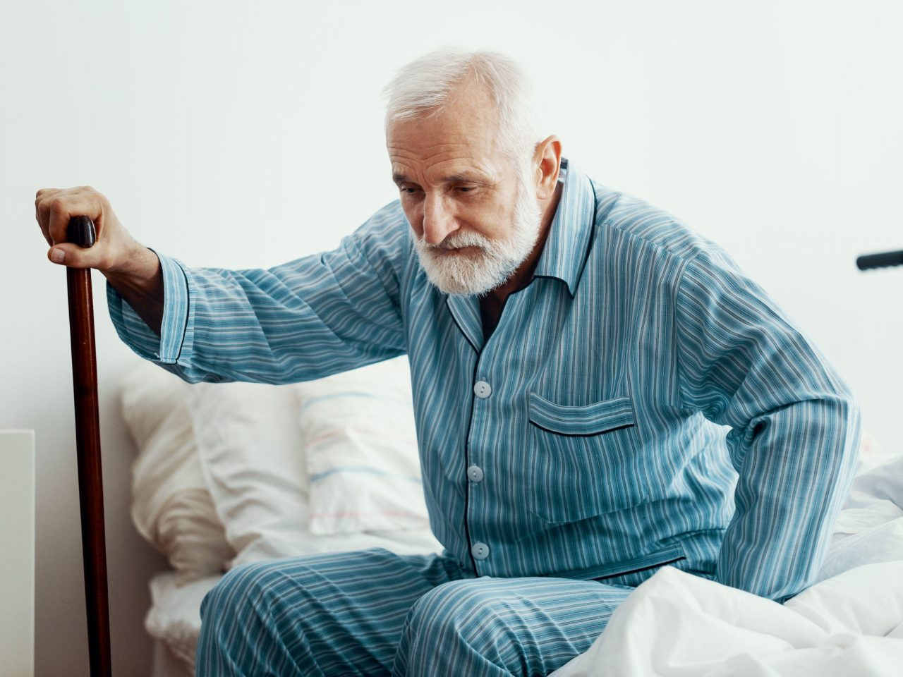 home visit mobile physiotherapy helping senior male in aged care get out of bed Action Home Rehab