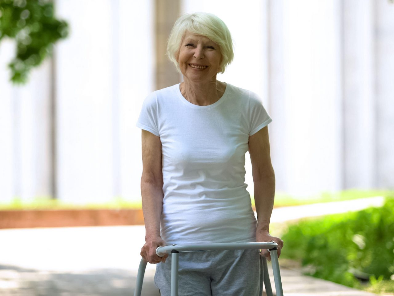 Home visit physiotherapy for female walking in park after surgery rehab Action Home Rehab